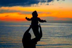 Familie bei Sonnenuntergang durch das Meer lizenzfreie stockfotografie