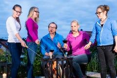 Familie beim Grillen abends im Garten Arkivfoton