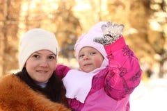 Familie: bemuttern Sie und die Tochter im Winter im Park Lizenzfreies Stockfoto