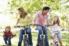 Familie berijdende fietsen stock foto's