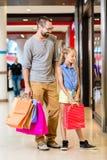 Familie bij winkelvenster in wandelgalerij Stock Fotografie