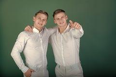 Familie, broederschap en vriendschapsconcept Twee broers die en vinger glimlachen richten royalty-vrije stock foto