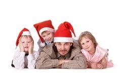 Familie in de kappen van Kerstmis Royalty-vrije Stock Afbeeldingen