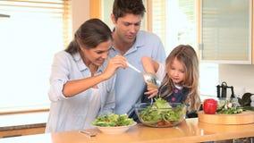 Familie in de keuken die een salade samen maken stock videobeelden