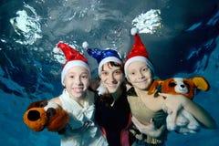 Familie: de moeder en twee dochters zwemmen en spelen onderwater in de pool bij de holdingsstuk speelgoed van kappensanta claus h stock afbeelding