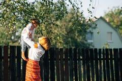 Familie: de moeder vervoert een jongen Zij zijn gekleed in geborduurde robes royalty-vrije stock foto