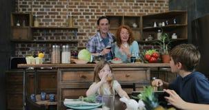 Familie in den Küchen-Uhr-lustigen Videos auf Tablet-Computer-Warteabendessen-Vorbereiten, Eltern-und Kinderkommunikation stock video footage
