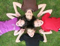 Familie der Geschwister, die auf dem Gras-Lachen liegen lizenzfreie stockfotos