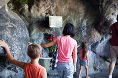 Familie in der Grotte in Lourdes Stockbilder