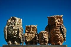 Familie der hölzernen Eulen auf blauem Himmel des Hintergrundes Stockfoto