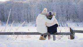Familie in der warmen Kleidung, die die Winterlandschaft bewundernd umarmt stock video