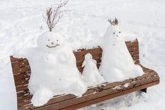 Familie des Schneemannes auf einer Bank Lizenzfreies Stockfoto