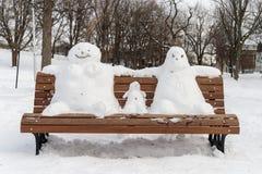 Familie des Schneemannes auf einer Bank Stockfoto