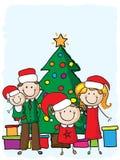 Familie dichtbij de Kerstmisboom Stock Foto