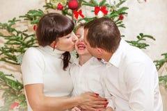 Familie dichtbij de Kerstmisboom Stock Afbeelding