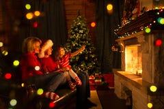 Familie dichtbij open haard en Kerstboom in feestelijk verfraaid huisbinnenland royalty-vrije stock afbeelding