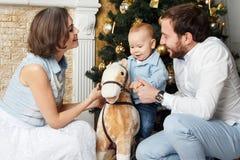Familie dichtbij thear nieuwe jaarboom Stock Afbeeldingen
