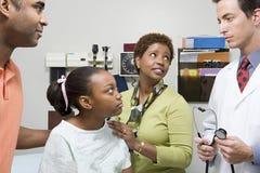 Familie die aan arts luisteren stock fotografie