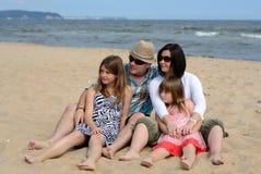 Familie die aan de strandkant kijkt Stock Afbeelding