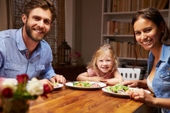 Familie, die Abendessen an einem Speisetische, Kamera betrachtend isst Lizenzfreie Stockfotos