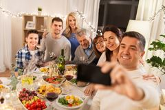 Familie, die Abendessen hat und selfie nimmt stockbild