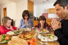Familie, die Anmut sagt, bevor das Mittagessen gegessen wird Stockfotos