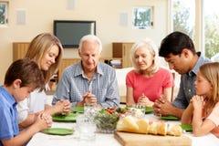 Familie, die Anmut vor Mahlzeit sagt Stockbild