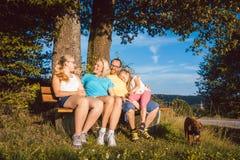 Familie, die auf Bank während eines weiten Spaziergangs im Sommer stillsteht Lizenzfreie Stockbilder