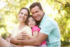 Familie, die auf Baum im Park sitzt Stockfoto