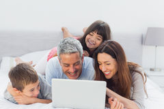 Familie, die auf Bett unter Verwendung ihres Laptops liegt Stockfoto