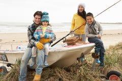 Familie, die auf Boot mit Angelrute auf Strand sitzt Lizenzfreie Stockfotos