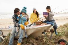 Familie, die auf Boot mit Angelrute auf Strand sitzt Lizenzfreie Stockfotografie