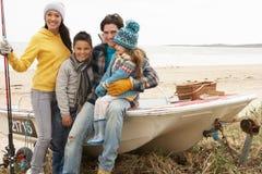 Familie, die auf Boot mit Angelrute auf Strand sitzt Stockfotografie