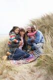 Familie, die auf Decke in den Dünen auf Winter-Strand sitzt Lizenzfreies Stockbild