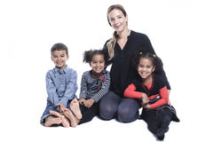 Familie, die auf dem Boden eines Fotografiestudios sitzt Stockfotos
