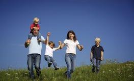 Familie, die auf dem Gebiet spielt mit Kindern geht Lizenzfreie Stockfotografie
