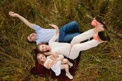 Familie, die auf dem Gras liegt und oben auf der Natur, glückliche Familie schaut Stockfotografie