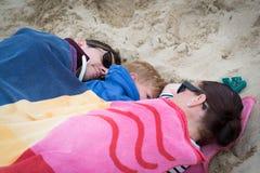 Familie, die auf dem kalten Strand schläft Stockfotografie