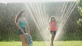 Familie, die auf dem Rasen-Wasser besprüht auf Mutter mit Kindern spielt stock video footage