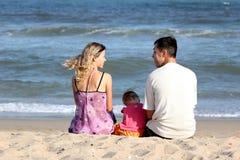 Familie, die auf dem Sand sitzt Stockbild