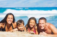 Familie, die auf dem Strand spielt Lizenzfreie Stockfotografie