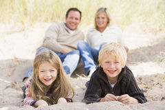 Familie, die auf dem Strandlächeln sich entspannt Lizenzfreies Stockfoto