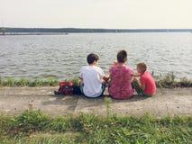 Familie, die auf dem Ufer des Sees sitzt Lizenzfreie Stockfotos