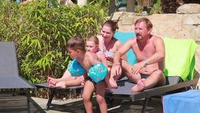 Familie, die auf den Sonnenruhesesseln stillsteht stock footage