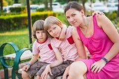 Familie, die auf der Bank sitzt Stockbild