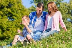 Familie, die auf der Wiese spielt mit Seifenblasen sitzt Stockfoto
