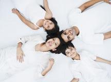 Familie, die auf einem Bett liegt Stockfoto