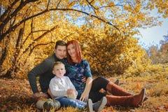 Familie, die auf einem Gras mit Kürbis sitzt Stockfoto