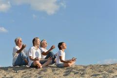 Familie, die auf einem Sand sitzt Stockbilder