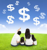 Familie, die auf einer Wiese mit Geld von Wolken sitzt stockfotos